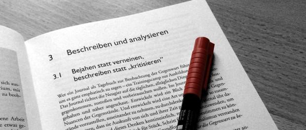 aufgeschlagenes Buch mit Stift